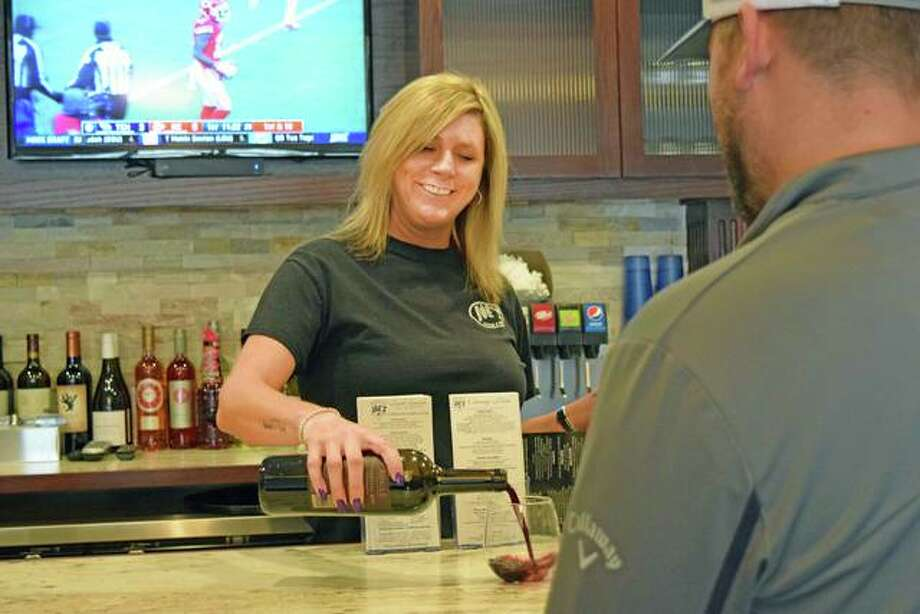 A six-year server at Joe's Pizza & Pasta, Candy Buie, pours a glass of red merlot for a customer on Tuesday afternoon in the business' new expansion in Edwardsville. Photo: Tyler Pletsch | The Intelligencer
