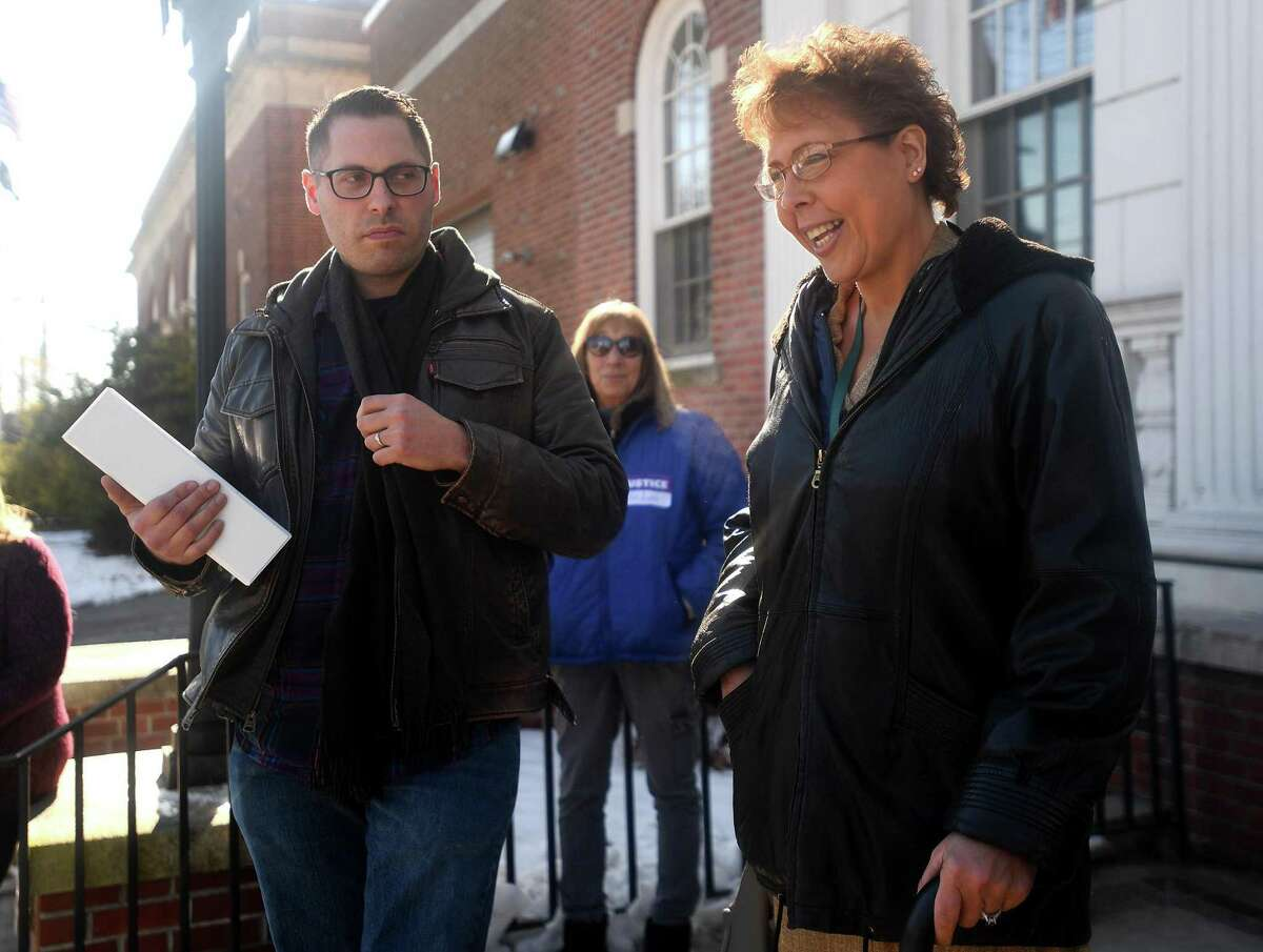 Standing with her brother Tim McLaughlin, Lori Wierzbicki of Milford smiles as she addresses supporters and the media outside Superior Court in Milford Wednesday.
