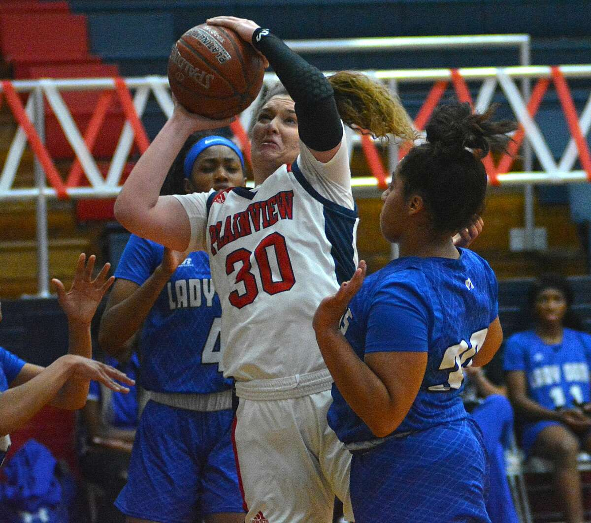 Plainview's Kylie Bennett puts in the shot between Amarillo Palo Duro defenders Sh'heneci Matthews (4) and Leyla Wright during their District 3-5A girls basketball game on Tuesday in the Dog House.