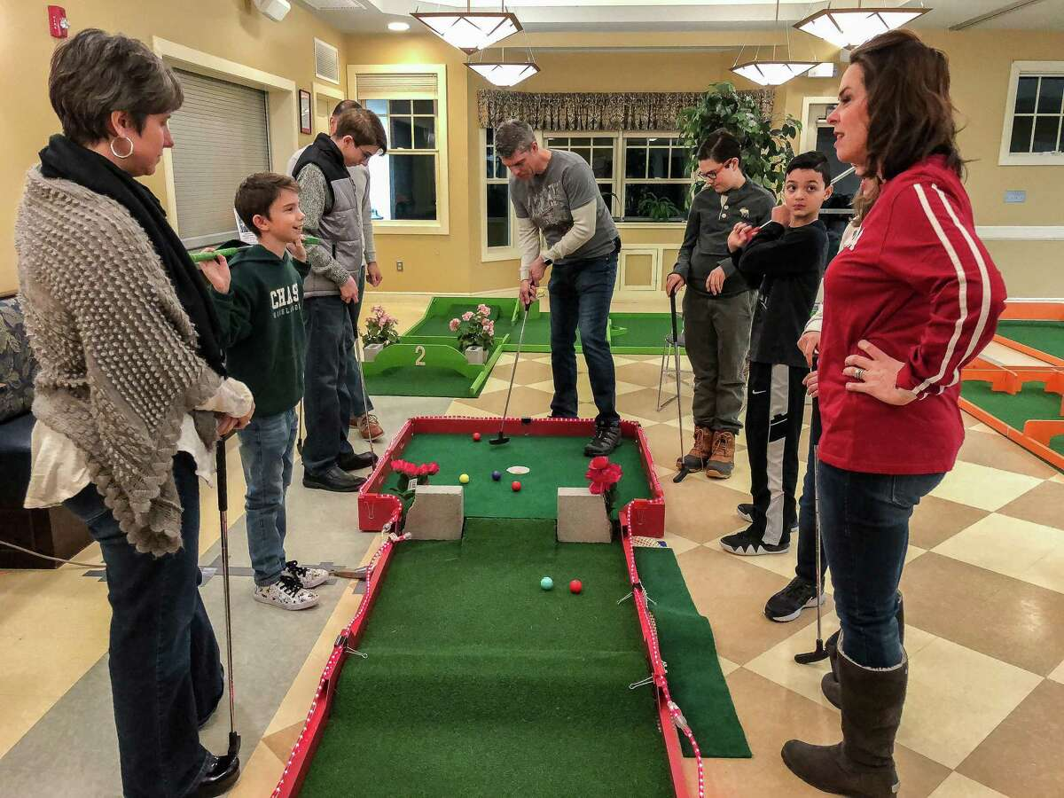 Families and friends at last year's event enjoying a round of indoor mini golf in Woodbury.
