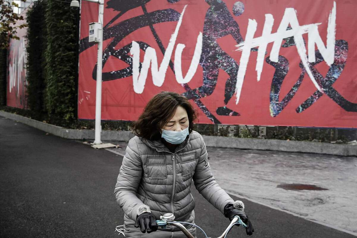 WUHAN, CHINA - JANUARY 22: (CHINA OUT) A woman wears a mask while riding a bicycle on January 22, 2020 in Wuhan, Hubei province, China. A new infectious coronavirus known as