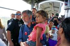 Witness at the Border and Global Refugee Advocate Thomas Cartwright carries a migrant child across the Gateway International Bridge from Matamoros, Mexico to Brownsville, Texas, Jan. 17, during a congressional delegation visit to the migrant camps in Matamoros, Mexico. By blocking refugees from Texas, the state is denying itself major growth opportunities.