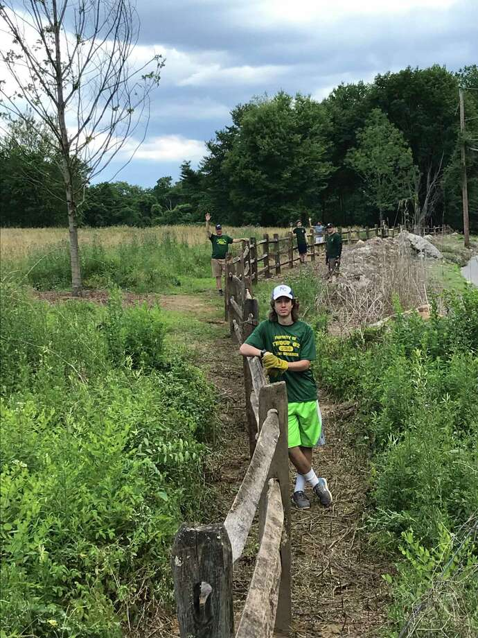 Owen Weber at the fence he and other volunteers installed at an Audubon Society property in Westport. Photo: Contributed Photo