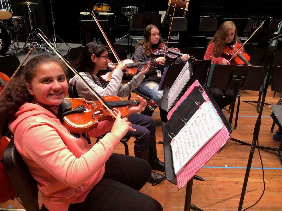 Shelton Intermediate School violinists Jess Almezel, Shreya Yadav, Kaylee Cooney and Keeley Haughie practice before the school's winter arts festival Thursday, Jan. 16.