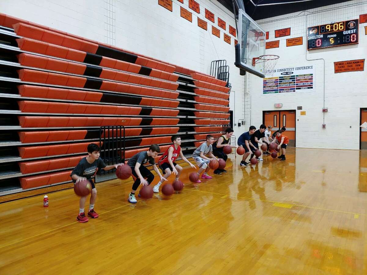 Players practice dribbling during the Shelton High shooting clinic on Monday, Jan. 20. Varsity players taught younger kids basketball skills and collected food for the Audrey Dreyer Food Bank in the process.