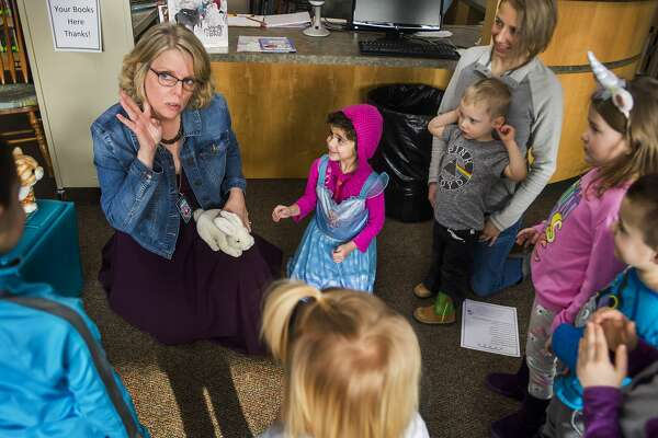 Diana Ball, librarian at St. Brigid Catholic School, recites a rhyme with a group of children during a preschool story hour Wednesday, Jan. 22, 2020 at the school. (Katy Kildee/kkildee@mdn.net)