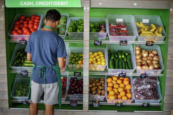 FILE - In this Aug. 21, 2019, file photo a worker stocks a produce stand at a metro station in Atlanta. Throwing away food is throwing away money. And with most wasted food winding up in landfills, ita€™s not great for the environment, either. (AP Photo/David Goldman, File)