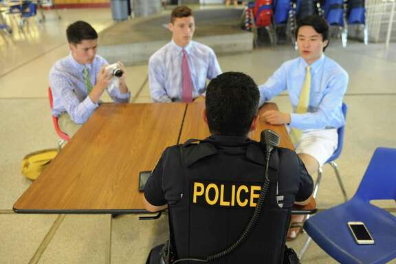 "Graduating seniors Marcus Zabik, left, Jack Freiheit, center, and Naoya Fukuchi interview and photograph School Resource Officer Carlos Franco for their ""Humans of Greenwich"" senior project at Greenwich High School in Greenwich, Conn. Wednesday, June 17, 2015. Based on photographer Brandon Stanton's ""Human's of New York,"" the three GHS students photograph and interview students, teachers and other Greenwich residents to put on their Facebook page, which has gathered over 1,000 followers."