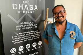 """TheChagoCompany, a new permanent pop-up at Fearless Coffee on 303 Second St, claims to be the """"first-ever mushroom cafe"""" in San Francisco. Founderand creator Gavin Escolar poses with the Chago Company sign at their grand opening on Wednesday."""