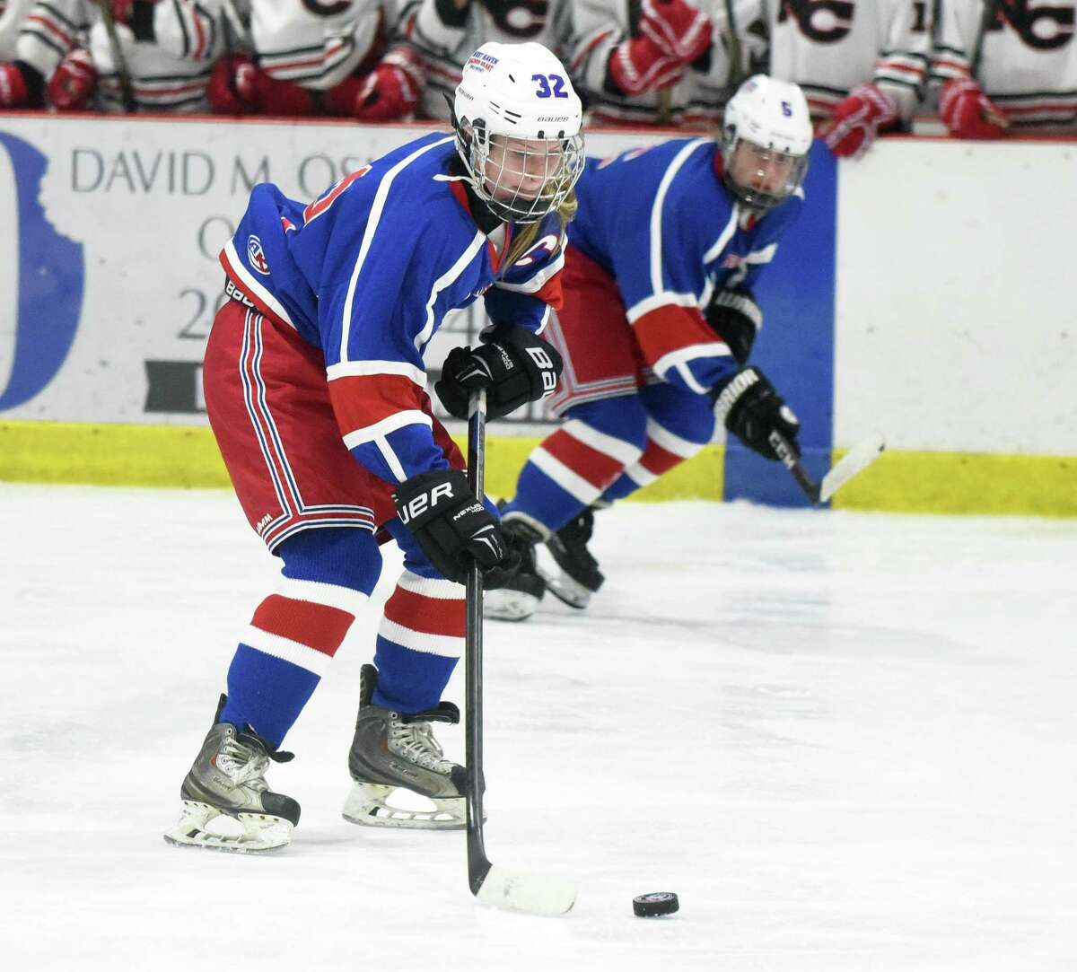 West Haven/SHA's Megan Froehlich (32) carries the puck into the offensive zone as linemate Jianna Cohrs (5) follows along the boards against New Canaan during a game in January.