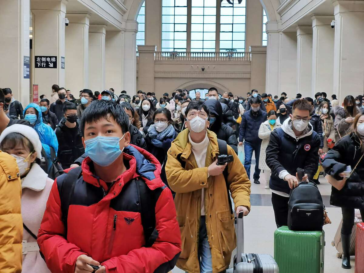 """People wear face masks as they wait at Hankou Railway Station on January 22, 2020 in Wuhan, China. A new infectious coronavirus known as """"2019-nCoV"""" was discovered in Wuhan last week. Health officials stepped up efforts to contain the spread of the pneumonia-like disease which medical experts confirmed can be passed from human to human. Cases have been reported in other countries including the United States,Thailand, Japan, Taiwan, and South Korea. It is reported that Wuhan will suspend all public transportation at 10 AM on January 23, 2020."""