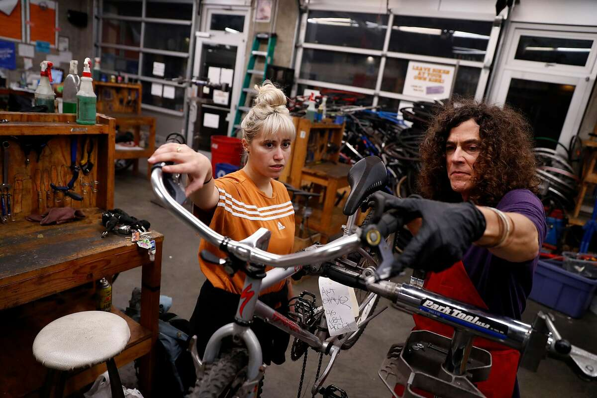 Emily Croft (left) is helped by volunteer Blase Bova during Women, Trans* and Femme Night at San Francisco Bike Kitchen in San Francisco, Calif., on Monday, January 13, 2020.