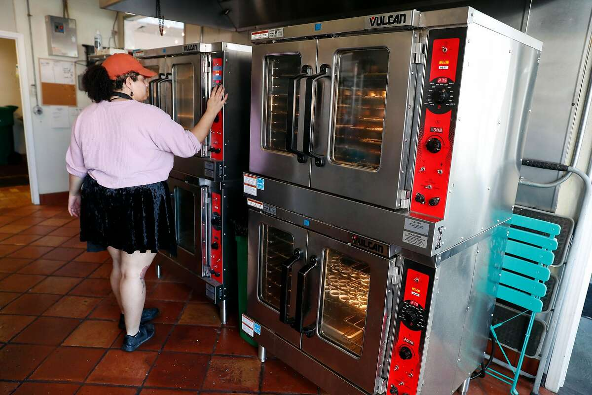 Dominik Andrews (cq) makes cupcakes in an all-electric oven at James the Giant Cupcake in Jack London Square in Oakland, Calif., on Wednesday, January 22, 2020.