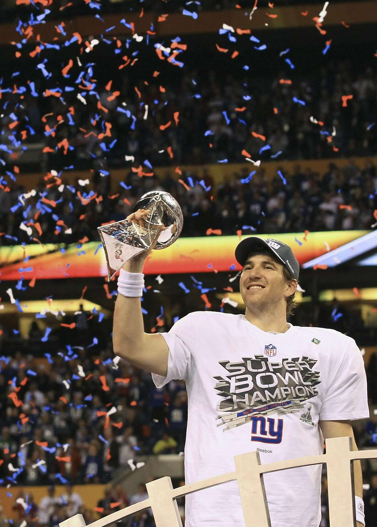 FILE -- Eli Manning of the New York Giants holds the Vince Lombardi Trophy after winning Super Bowl XLVI at Lucas Oil Stadium in Indianapolis, Feb. 5, 2012. Manning, who became a New York sports folk hero after he led the Giants to two upset victories in the Super Bowl, is retiring from the NFL, the team said on Jan. 22, 2020. (Doug Mills/The New York Times)