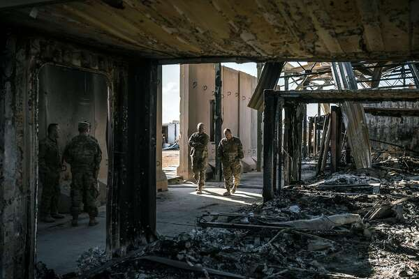 "FILE -- U.S. military personnel survey the damage to a building that was struck by Iranian missiles at Al Asad Air Base in Anbar, Iraq, Jan. 13, 2020. Trump on Jan. 22 dismissed concussion symptoms reported by several American troops after Iranian airstrikes on Al Asad Air Base as ""not very serious,"" even as the Pentagon acknowledged that a number of service members were being examined for possible traumatic brain injury caused by the attack. (Sergey Ponomarev/The New York Times)"