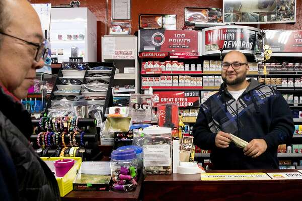 Asad Sharifi of Cheaper Cigarettes makes a sale while in his shop along Noriega Street in San Francisco, Calif. Wednesday, Jan. 22, 2020. The first-in-the-nation ban on the sale of e-cigarettes takes effect in San Francisco on January 29, 2020, but shop owners like Sharifi are already taking a hit in sales.