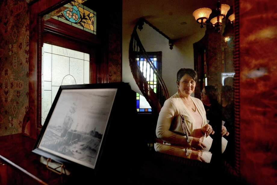 Carrie Weaver looks at a picture of old ships on the Neches River set out on the entry fireplace during a re-opening ceremony at the historic Sanders-McNeill home in Beaumont Wednesday. The event was one of two such celebrations that took place downtown, as the Tyrrell Historical Library held its public grand re-opening and ribbon-cutting ceremony later Wednesday afternoon.