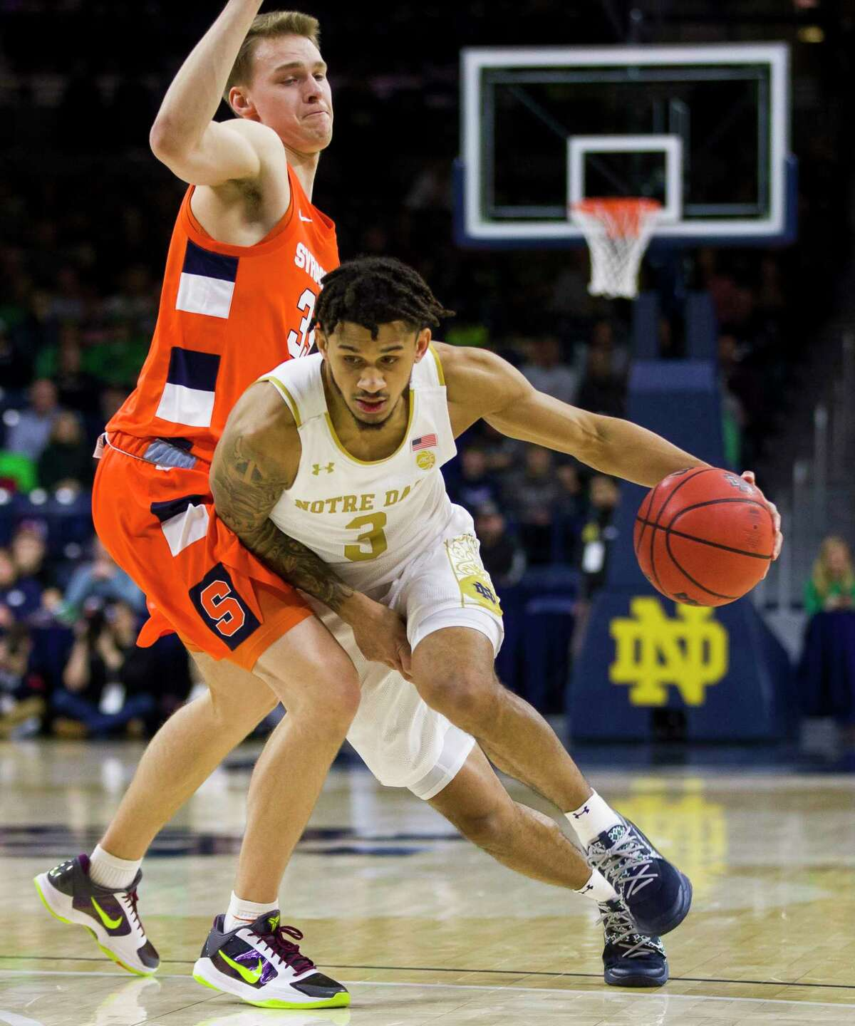 Notre Dame's Prentiss Hubb (3) drives by Syracuse's Buddy BoeheimA (35) during the first half of an NCAA college basketball game Wednesday, Jan. 22, 2020, in South Bend, Ind. (AP Photo/Robert Franklin)