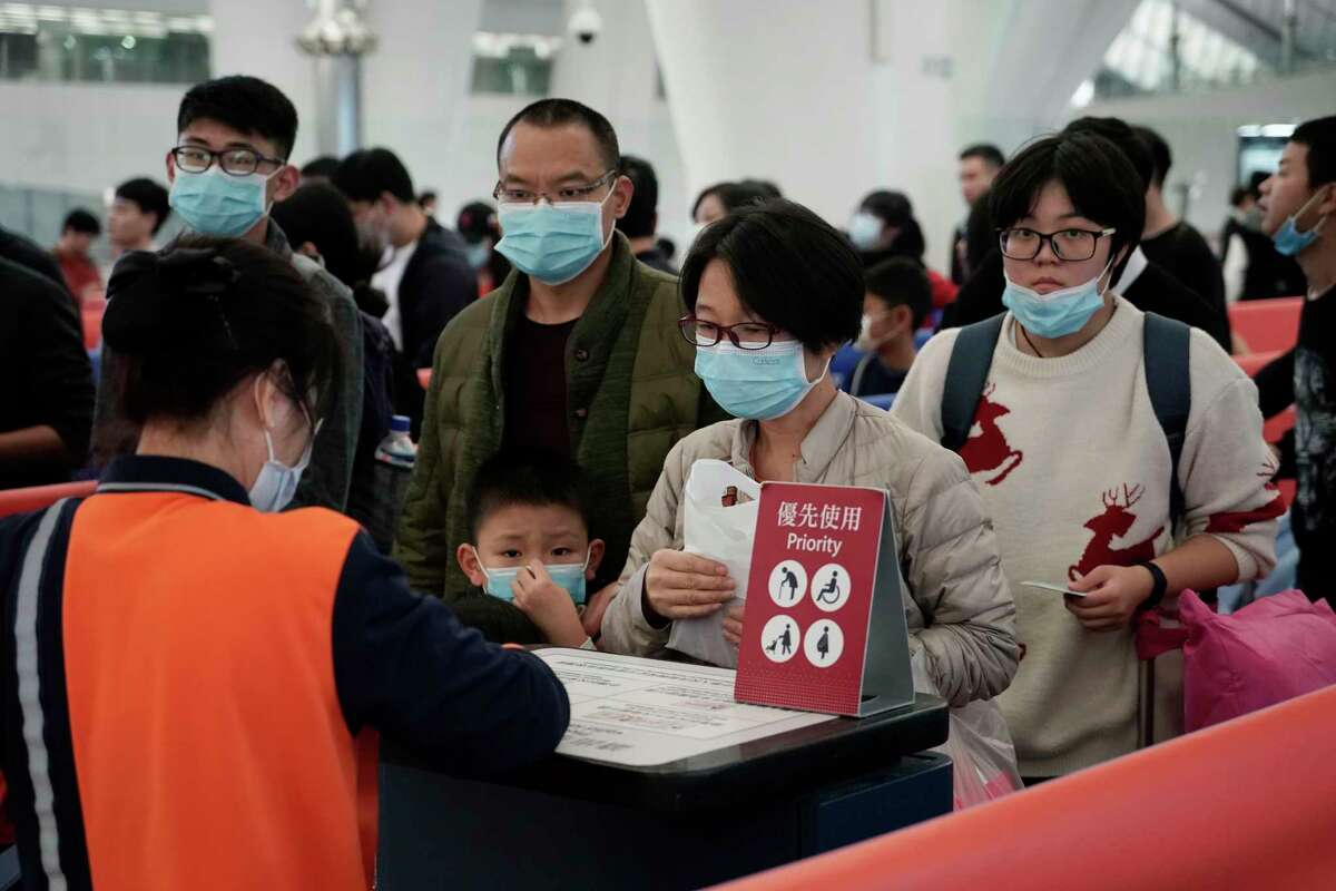 Passengers wear masks to prevent an outbreak of a new coronavirus in the high speed train station, in Hong Kong, Wednesday, Jan. 22, 2020. The first case of coronavirus in Macao was confirmed on Wednesday, according to state broadcaster CCTV. The infected person, a 52-year-old woman, was a traveller from Wuhan.