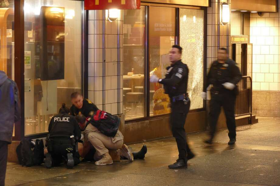Officers attend to one of several shooting victims, outside of McDonald's on Third Avenue, Wednesday, Jan. 22, 2020, in Seattle. The window of the restaurant behind them was shattered after a gunman opened fire in the heavily trafficked downtown area. (David Silver via AP) Photo: David Silver/AP