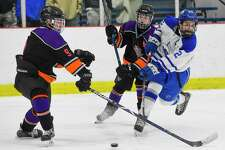 Darien's Bennett McDermott (22) slaps a shot past Stamford Westhill Co-op's Tyler Tuccinardi (9) towards the goal in the second period of an FCIAC boys hockey game at the Darien Ice House on Jan. 22, 2020 in Darien Connecticut. McDermmott scored three goals, including the game winning goal in over time for the Bluewaves 5-4 OT win.