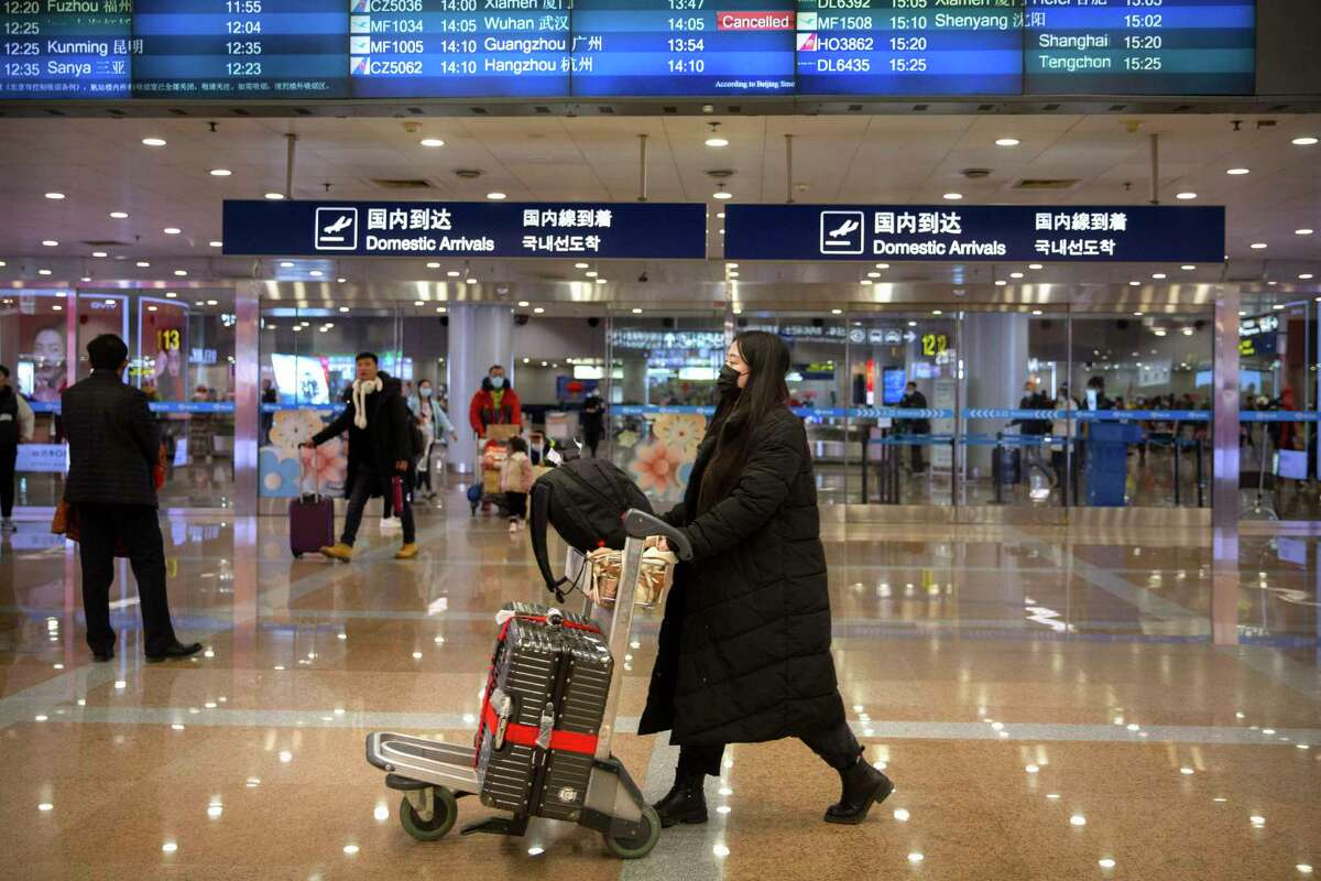 Travelers in face masks walk past a display board showing a canceled flight from Wuhan at Beijing Capital International Airport in Beijing, Thursday, Jan. 23, 2020. China closed off a city of more than 11 million people Thursday, halting transportation and warning against public gatherings, to try to stop the spread of a deadly new virus that has sickened hundreds and spread to other cities and countries in the Lunar New Year travel rush.