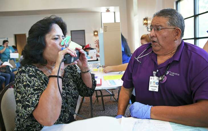 Luciano Valdez, a respiratory therapist from Christus Santa Rosa, coaches Lydia Mireles as she draws a big breath to test her capacity during a health fair in 2015.