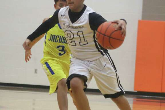 San Jacinto 7A player Aurelio Morales dribbles past Jackson's defense during Wednesday night's game at Queens. Morales scored five first-half points.