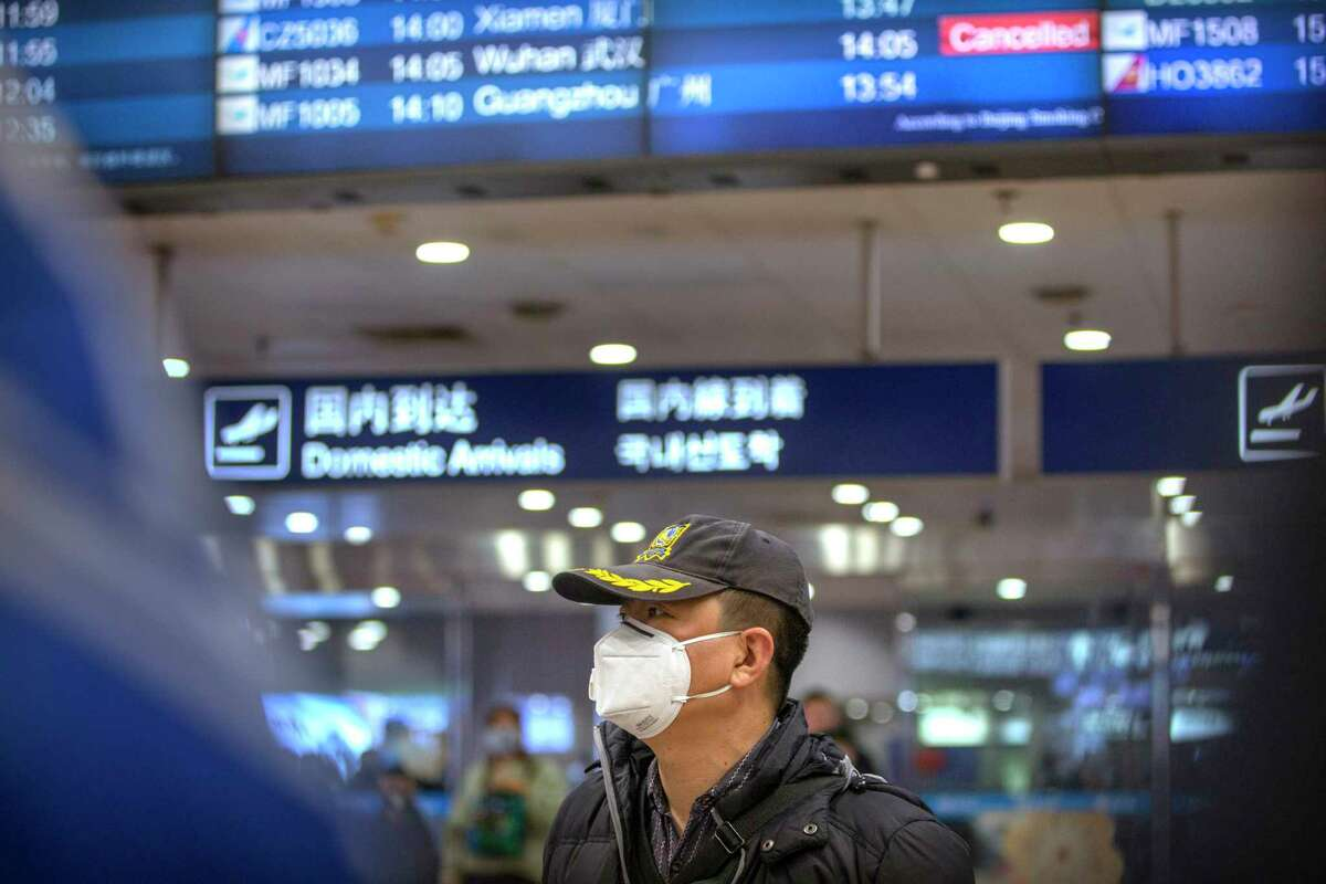 A traveler wears a face mask beneath an information display showing a canceled flight from Wuhan at Beijing Capital International Airport in Beijing, Thursday, Jan. 23, 2020. China closed off a city of more than 11 million people Thursday, halting transportation and warning against public gatherings, to try to stop the spread of a deadly new virus that has sickened hundreds and spread to other cities and countries in the Lunar New Year travel rush.