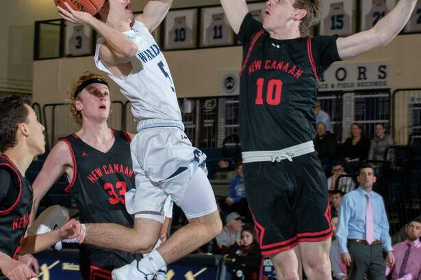 Tucker Walden goes up for a shot during Wilton's overtime loss to New Canaan on Tuesday night.