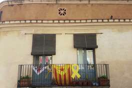 On a balcony: the official flag of Catalonia bookended by yellow ribbons that protest the jailing of pro-independence politicians.