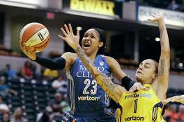 Minnesota Lynx's Maya Moore, left, shoots against Indiana Fever's Jazmon Gwathmey during the first half of a WNBA basketball game in Indianapolis on Aug. 30, 2017.