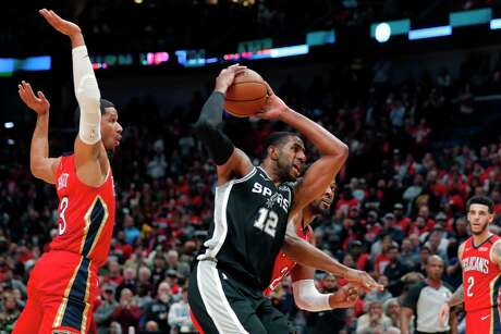 San Antonio Spurs' LaMarcus Aldridge (12) goes to the basket against New Orleans Pelicans guard Josh Hart (3) and forward Derrick Favors in the second half of an NBA basketball game in New Orleans, Wednesday, Jan. 22, 2020. The Spurs won 121-117.