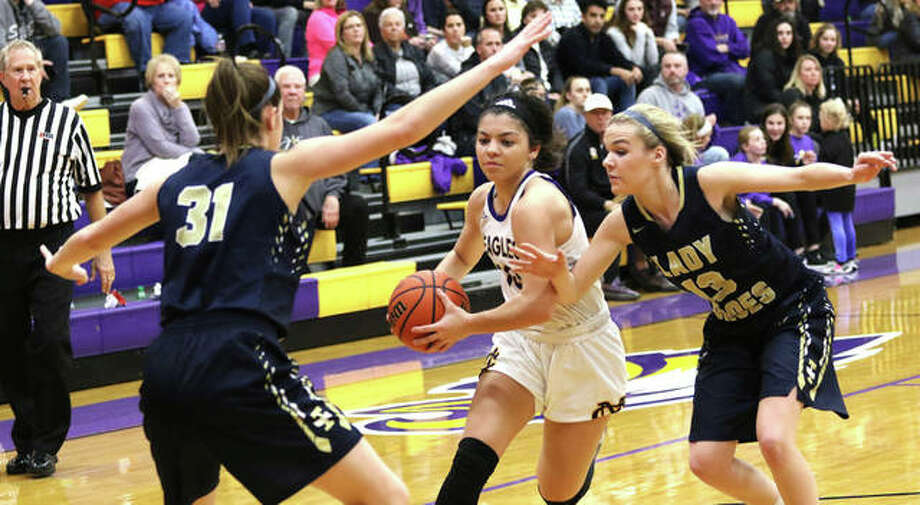 CM's Kourtland Tyus drives between Teutopolis's Morgan Mette (left) and Ciara Roepke (right) during a Jan. 13 Eagles victory in Bethalto. The teams met again Wednesday night at the Highland Tourney semifinals and the Eagles won again, 42-34. Photo: Greg Shashack / The Telegraph