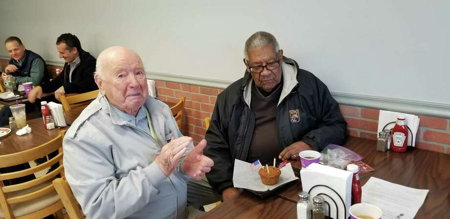 Trygve Hanson, left, and Doug Jones contemplate the cupcake commemorating their 98th and 95th birthdays, respectively. Photo: Jeff Turner / Contributed Photo