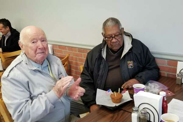 Trygve Hanson, left, and Doug Jones contemplate the cupcake commemorating their 98th and 95th birthdays, respectively.