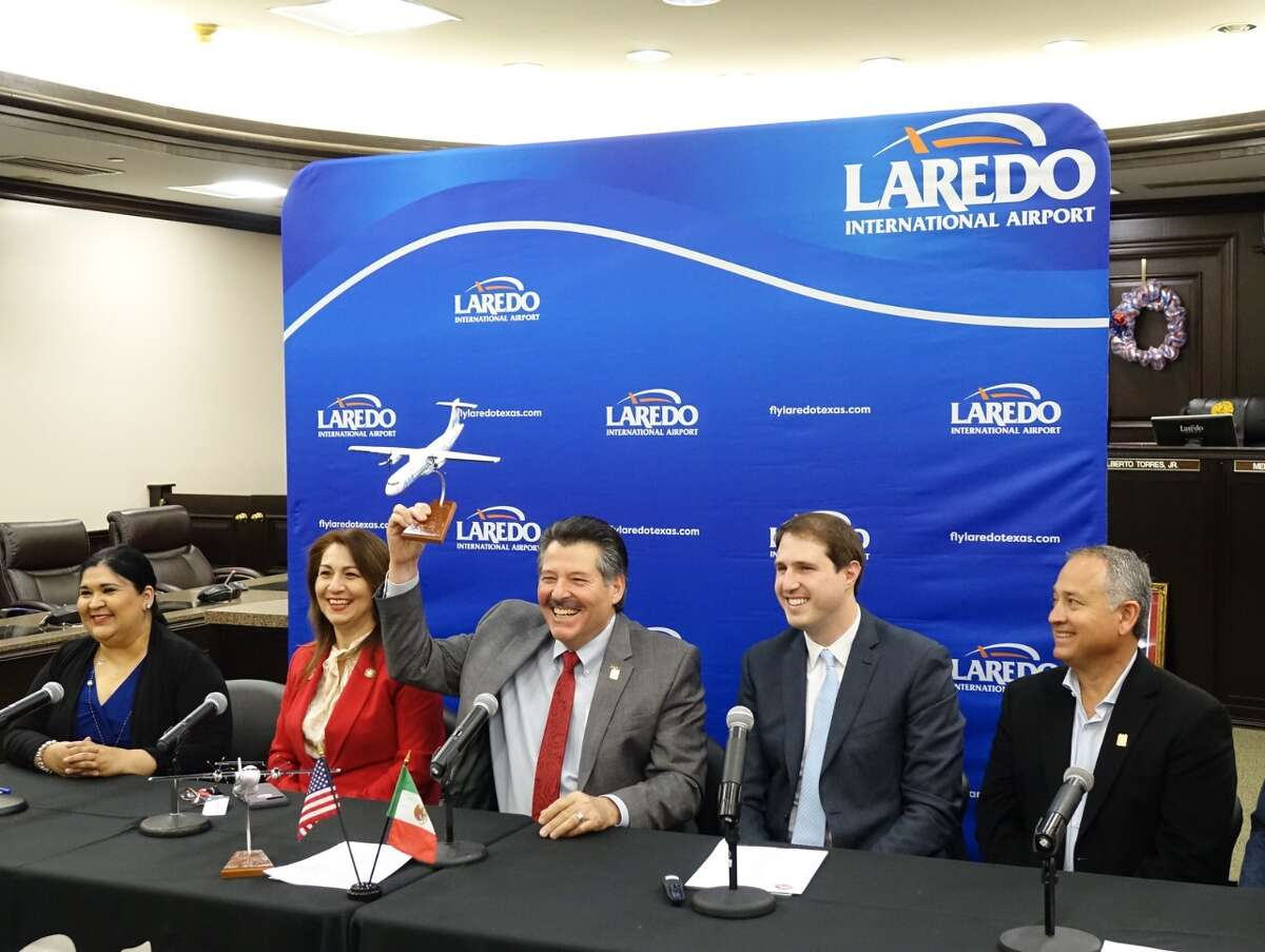 """Laredo Mayor Pete Saenz holds up an Aeromar airplane statue on Wednesday during the announcement of direct flights from Laredo to Mexico City that will be offered in the future through the Laredo Airport. He is joined at the table by Co-Interim City Manager Rosario Cabello, District 5 Councilmember Nelly Vielma, Aeromar Commerical Director Juan Rosello and Distirct 3 Councilmember Mercurio """"Merc"""" Martinez III."""