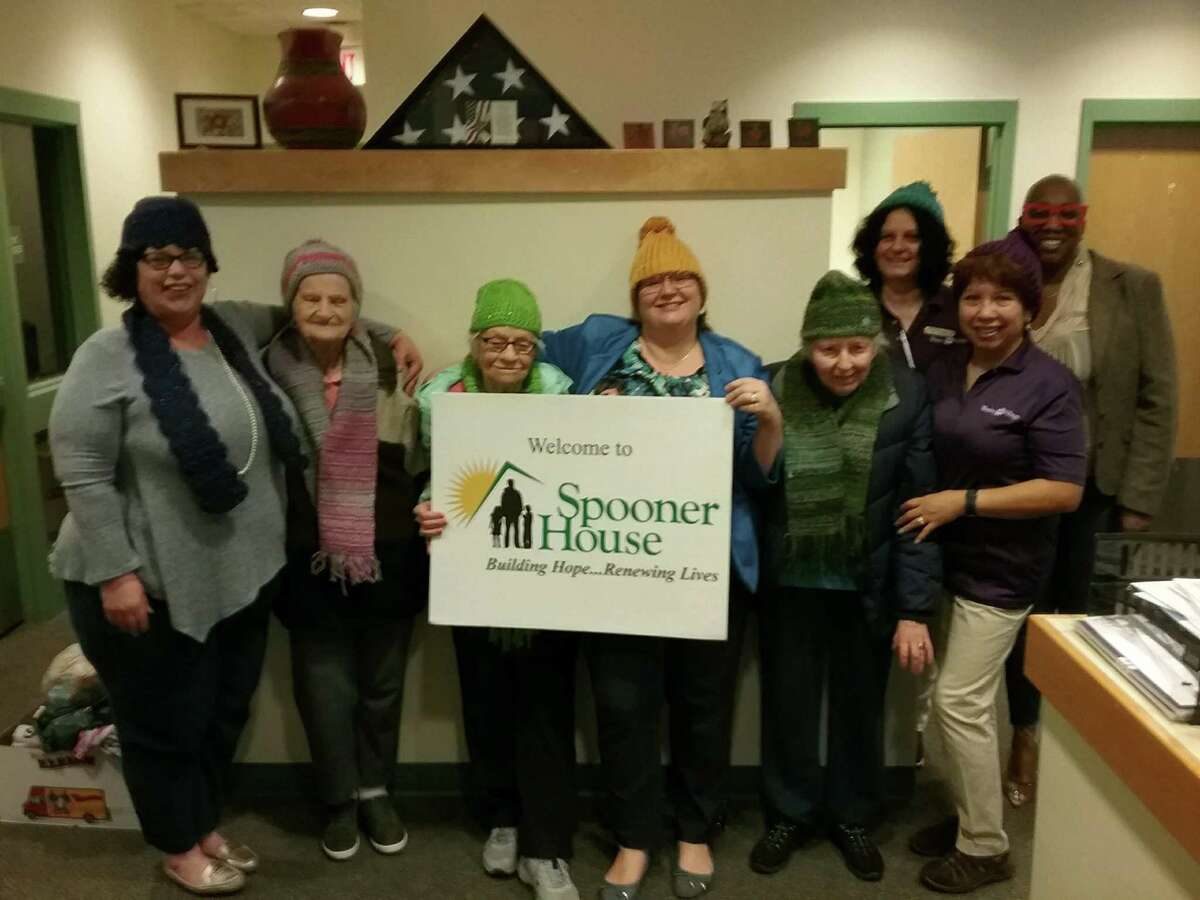 Residents and staff from Wesley Village pose with team from Spooner House after delivering hats and scarves for their clients.