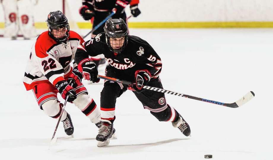 New Canaan's Eric Wills (5) breaks out with the puck while Fairfield's Rhys Davies (22) defends during a boys ice hockey game at the Wonderland of Ice in Bridgeport on Wednesday, Jan. 22, 2020. Photo: Stacy Mettler / New Canaan Hockey/Contributed / Stacy Mettler