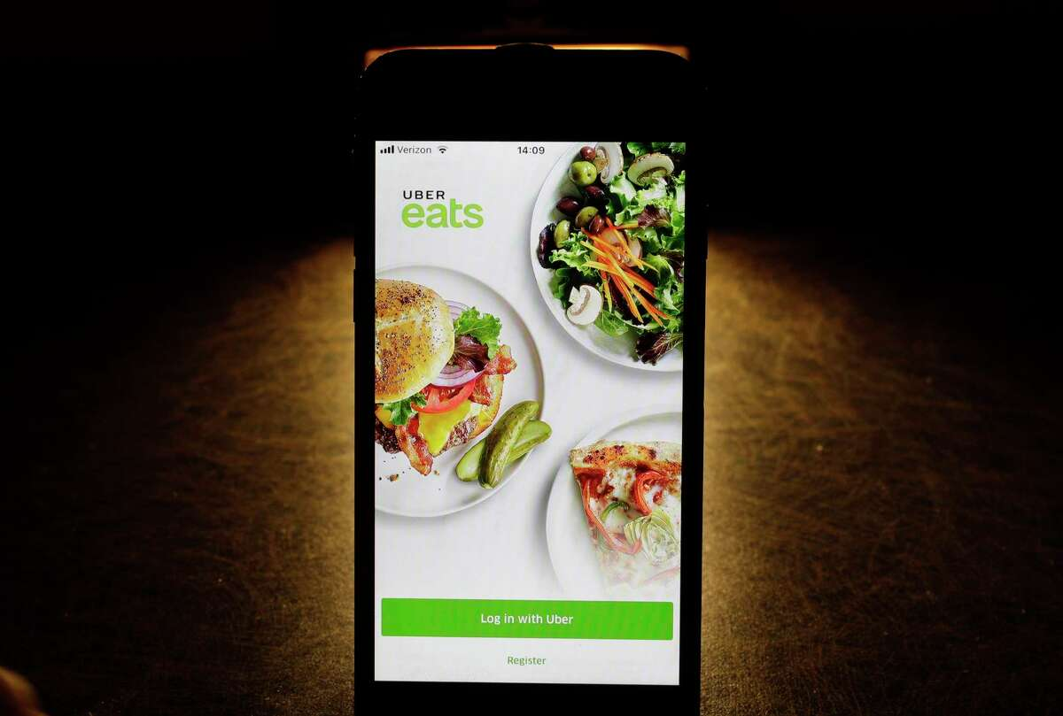 In this Feb. 20, 2018, file photo shows the Uber Eats app on an iPhone in Chicago. Uber is testing restaurant food deliveries by drone. The company's Uber Eats unit began the tests in San Diego with McDonald's and plans to expand to other restaurants later this year.