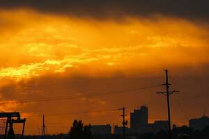 The sun sets behind the Midland skyline as pumpjacks work outside the city limits Thursday, Sept. 15, 2016. Oil and gas operators' efforts to become cash-flow positive are beginning to pay off and could boost the mergers and acquisitions market, giving operators capital for activity.
