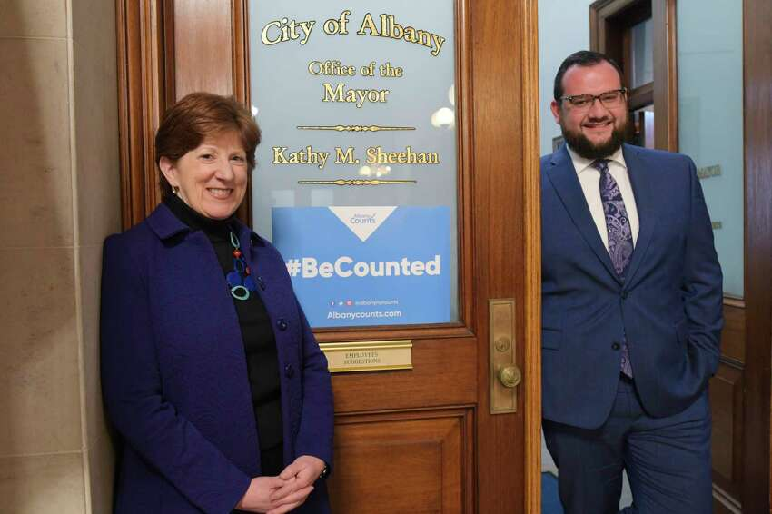 Mayor Kathy Sheehan, left, and her chief of staff, David Galin, pose next to a sign promoting the census on the door to the Mayor's office at City Hall on Wednesday, Jan. 15, 2020, in Albany, N.Y. (Paul Buckowski/Times Union)