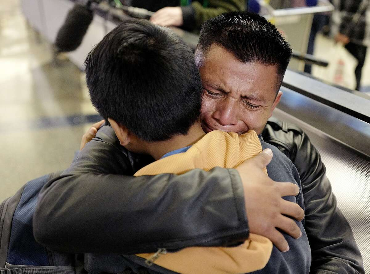 A man hugs his son at Los Angeles International Airport in January, about a year and a half after they were separated as part of the Trump administration's immigration policies.