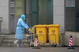 Staff move bio-waste containers past the entrance of the Wuhan Medical Treatment Center, where some infected with a new virus are being treated, in Wuhan, China, Wednesday, Jan. 22, 2020. The number of cases of a new coronavirus from Wuhan has risen over 400 in China Chinese health authorities said Wednesday.