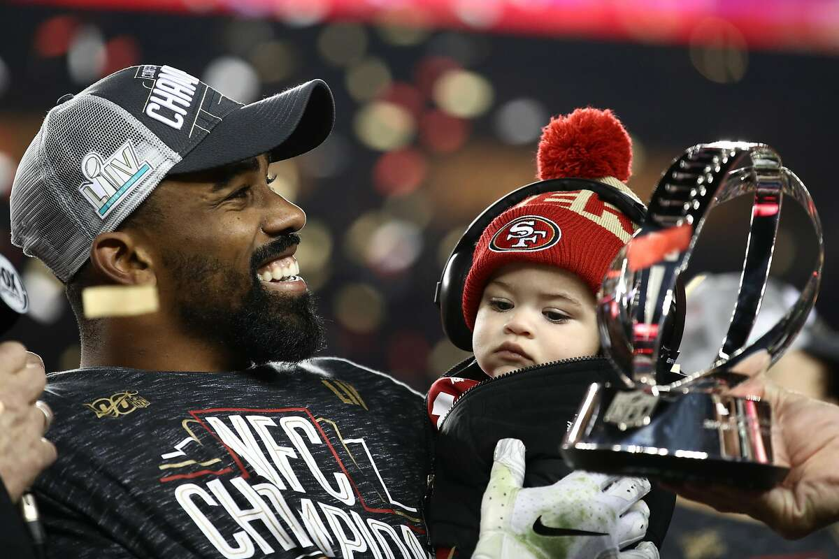 SANTA CLARA, CALIFORNIA - JANUARY 19: Raheem Mostert #31 of the San Francisco 49ers celebrates with the George Halas Trophy while holding his son, Gunnar, after winning the NFC Championship game against the Green Bay Packers at Levi's Stadium on January 19, 2020 in Santa Clara, California. The 49ers beat the Packers 37-20. (Photo by Ezra Shaw/Getty Images)