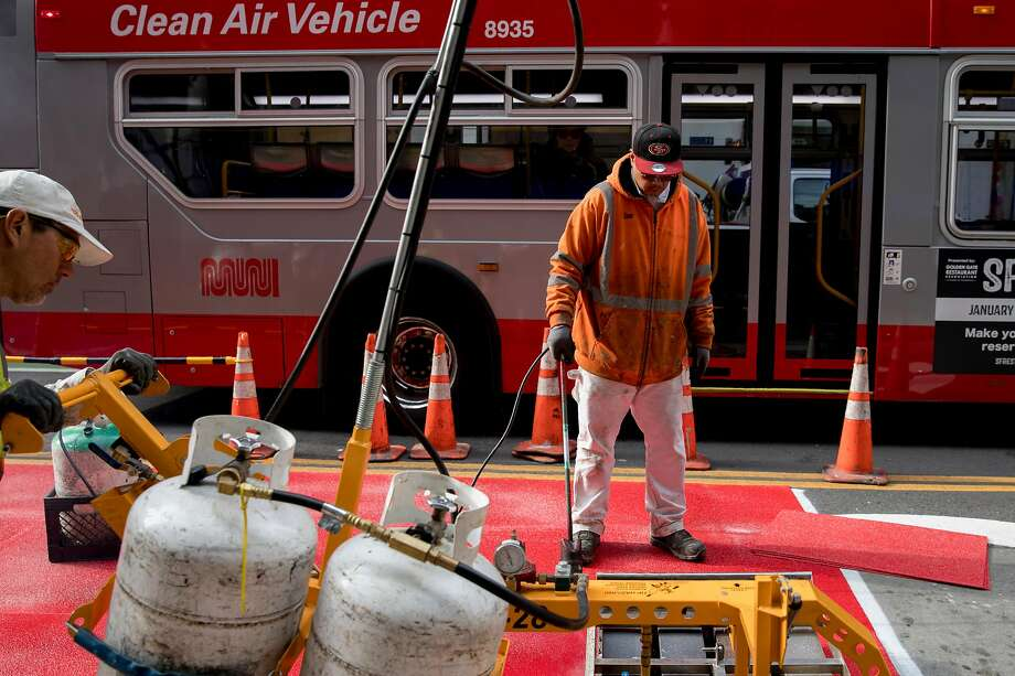 Municipal Transportation Agency crew member Ron Aquito (right) uses a blowtorch to melt down red paneling on a bus-only lane while Rene Menjivar (left) goes over it with another melting machine along Second Street leading to Market Street. Photo: Jessica Christian / The Chronicle