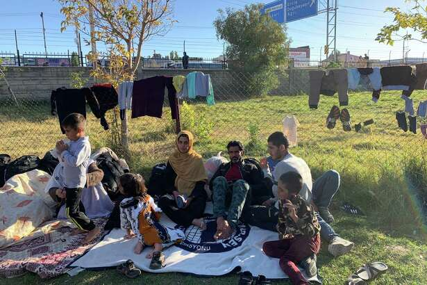 Samira Tajik, shown wearing a yellow headscarf, lived for years in Iran after fleeing conflict in Afghanistan. Tajik, 24, and her extended family, including her husband and three children, recently crossed into Turkey. This grassy lot at the bus station in Van, a city in eastern Turkey, now is a de facto camp for Afghan refugees.
