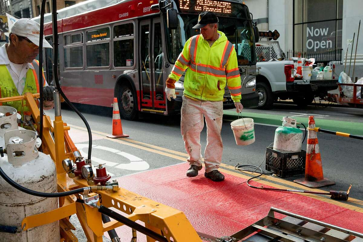SFMTA crew member Allan Young sprinkles binding materials as his colleagues lay down red striping on a bus-only lane along 2nd Street leading to Market Street in San Francisco, Calif. Thursday, Jan. 23, 2020. Beginning January 29, 2020, private vehicles will be banned from driving on Market Street with access only given to taxis and buses.