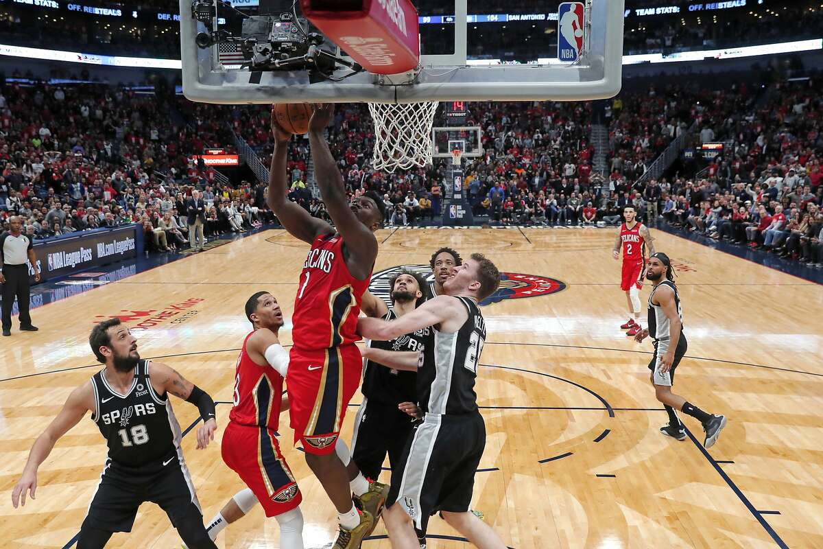 New Orleans Pelicans forward Zion Williamson (1) goes to the basket between San Antonio Spurs guard Marco Belinelli (18) and center Jakob Poeltl (25) in the second half of an NBA basketball game in New Orleans, Wednesday, Jan. 22, 2020. The Spurs won 121-117. (AP Photo/Gerald Herbert)