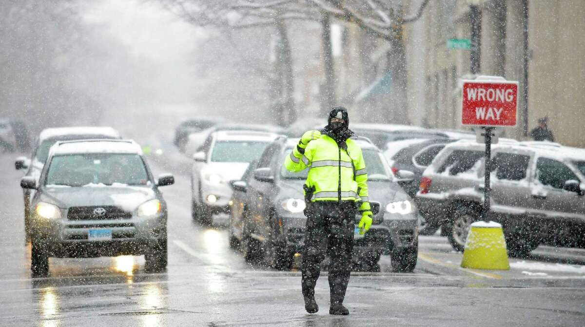Greenwich Police Officer Grant Cunningham bundles up as he braves the wintry conditions while directing traffic along Greenwich Avenue in Greenwich, Conn. on Dec. 9, 2017.